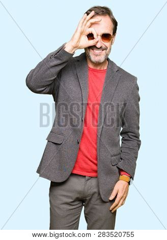 Middle age handsome business man wearing sunglasses doing ok gesture with hand smiling, eye looking through fingers with happy face.