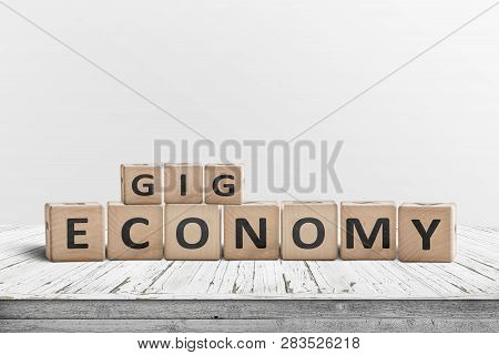 Gig Economy Sign Made Of Wood On A Worn Table With White Painted Planks
