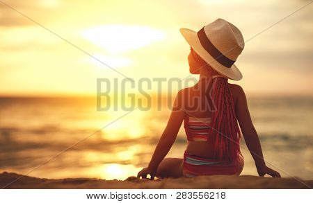 Happy Child Girl  In Swimsuit And Hat Sitting On The Beach At Sunset