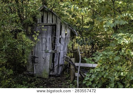 Old Wooden Corn Crib. Weathered And Worn Corn Crib Surrounded By Vintage Antique Farm Tools.