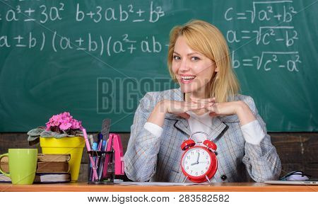 Teacher With Alarm Clock At Blackboard. Time. Study And Education. Modern School. Knowledge Day. Wom