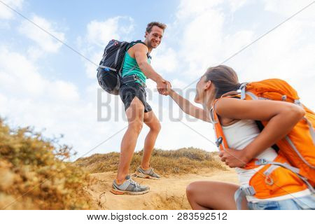 People hiking man helping woman climbing up hill on mountain hike. Helping hand team support friend supporting success trek for girl.
