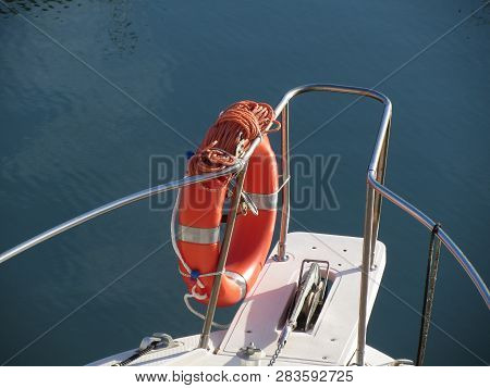 Boat Prow With Orange Lifebelt On The Sea Water . Rescue Concept