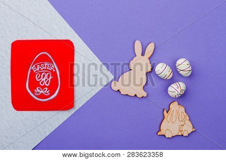 Plywood rabbit cutouts and eggs. Wooden cutout figurines of Easter rabbits and polystyrene eggs on colorful background. Red paper card with picture of Easter egg. poster