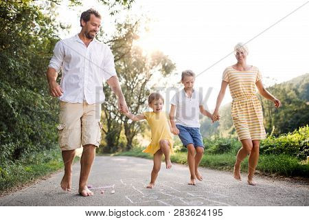 A Young Family With Small Children Playing Hopscotch On A Road In Summer.
