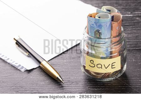 Euro notes and coins in a glass jar on a black wooden table with shiny reflection on a glossy surface. Money saving concept poster