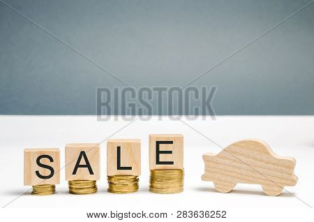 Coins And Wooden Blocks With The Word Sale And A Miniature Car. The Concept Of Saving Money To Buy A