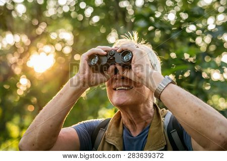 Elderly man watching birds with binoculars