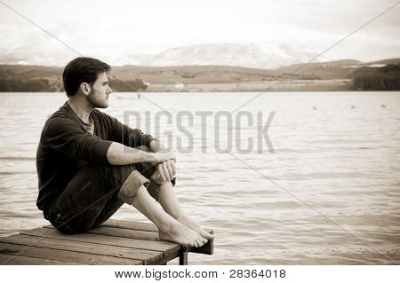 Young pensive man in nature background.