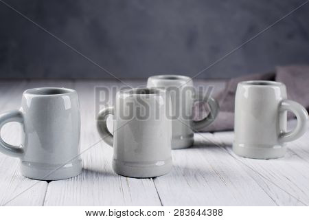 Set of grey rustic coffee cup handcraft against shabby grey wall. Natural  handmade crockery tableware poster