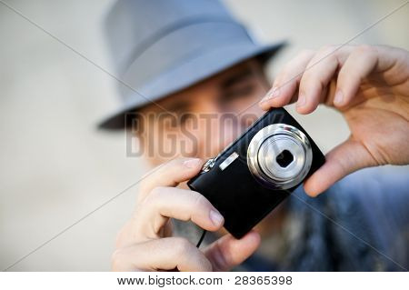 Young man wearing hat taking a picture using a camera