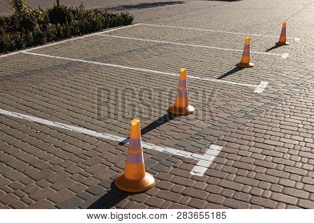 Orange Traffic Cones Standing In A Row Near The Parking
