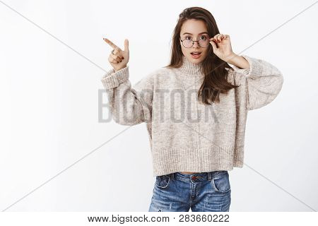Questioned And Impressed Cute Young 20s Woman Taking Off Glasses Intrigued As Pointing At Upper Left