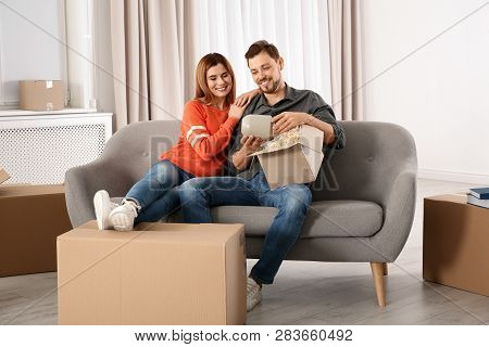 Couple Unpacking Cardboard Box While Resting On Sofa In Their New House. Moving Day