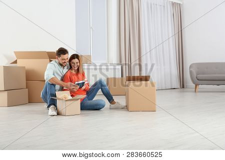 Couple Unpacking Moving Boxes In Their New House
