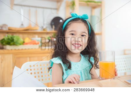 Little Asian Girl Smiling While Drinking Orange Juice At Breakfast Table In The Morning