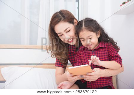 Beautiful Asian Mother And Daughter Using Tablet Computer Together At Home