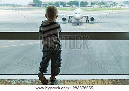 Little Baby Boy Waiting Boarding To Flight In Airport Transit Hall And Looking Through The Window At