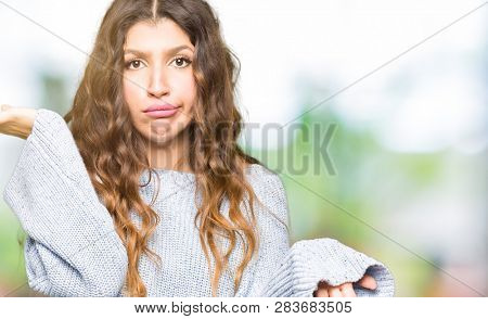Young beautiful woman wearing winter sweater clueless and confused expression with arms and hands raised. Doubt concept.
