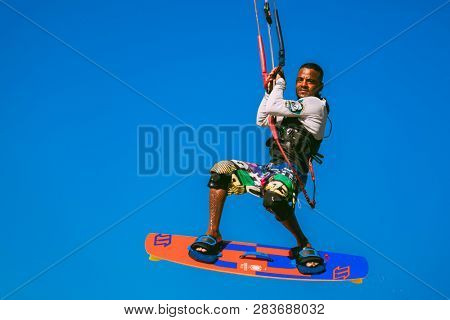 Egypt, Hurghada - 30 November, 2017: Close-up sportsman kitesurfer soaring in the blue sky. The surfer fully equipped with the board and kite elements in the air. The extreme professional flight.