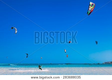 Egypt, Hurghada - 30 November, 2017: Numerous flying kites in the blue sky over the Red sea surface. The professional kitesurfers gliding on the waves. The water sport activity. Stunning marine scene.