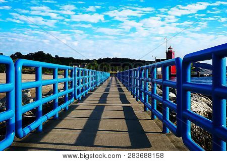 Holland Harbor Light. Painted In Oil. Bright Blue Fences On The Pier, Behind The Pier Are Green Fore