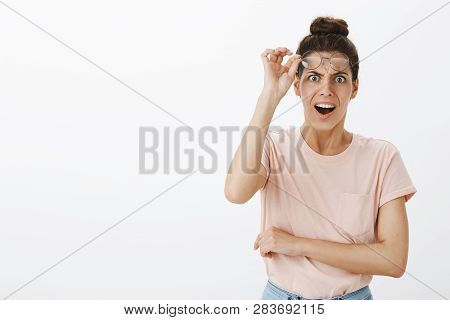 What Heck. Portrait Of Shocked Concerned And Insulted Young Bothered Woman Taking Off Glasses, Frown