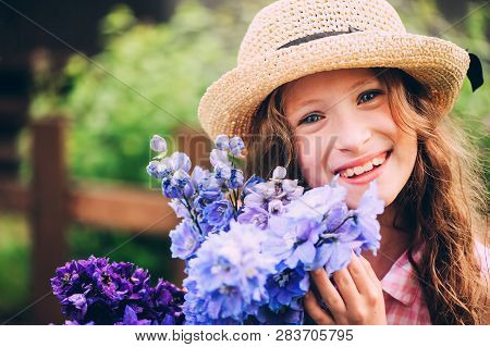 Romantic Portrait Of Happy Child Girl Picking Bouquet Of Beautiful Blue Delphinium Flowers From Summ