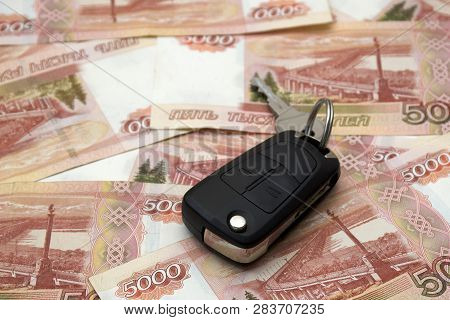 Black Car Key On A Horizontal Background Of A Variety Of Banknotes Of Five Thousand Russian Rubles.