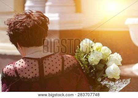 Beautiful Girl Holding Bouquet Of White Roses Flowers On Dating In The City. Businesswoman With Bunc