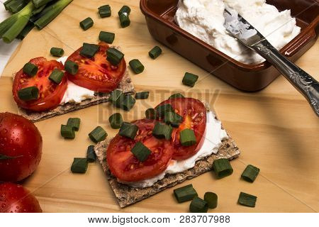 Healthy And Vegetarian Breakfast With Crispbread, Quark, Tomatoes And Spring Onions On A Wooden Boar