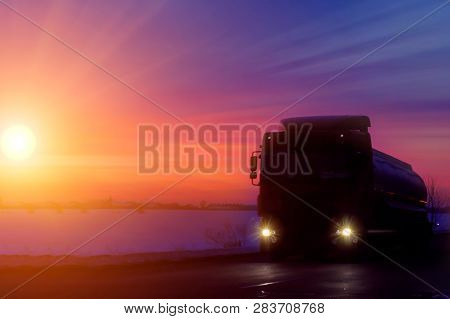 Silhouette Truck With Container On Highway, Cargo Transportation Concept. Sunset Background With Cop