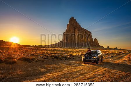 Shiprock, New Mexico, Usa - May 14, 2016 : Boy Enjoys Sunset At Shiprock Sitting On The Hood Of His