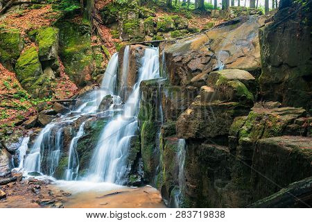 Waterfall In The Forest. Beautiful Spring Scenery. Water Comes Out Of Rocky Cliff. Wild Rapid  Strea