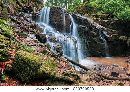 Waterfall In The Forest. Beautiful Spring Scenery. Water Comes Out Of Rocky Cliff. Mossy Rocks In Fr