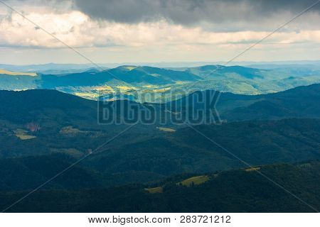Summer Mountain Scenery On An Overcast Day. Distant Ridge Beneath In Sunlight. Beautiful Landscape O