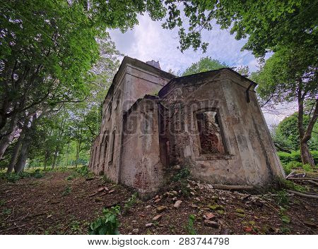 Old Abandoned St. Nicholas Church Ruins In Estonia. The Lush Foliage Of Trees And Forest Covering Th