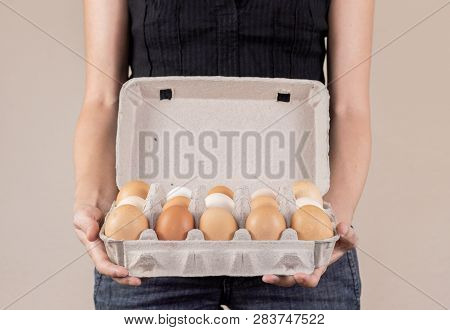Caucasian Woman With Black Shirt Holding A Cardboard Egg Box Full Of Hen Eggs