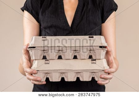 Caucasian Woman With Black Shirt Holding Two Cardboard Egg Boxes Full Of Hen Eggs.