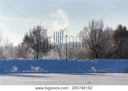 Beautiful Snowy Romantic Winter Landscape With Smoking Chimneys At Heating Plant Among Trees, Frozen