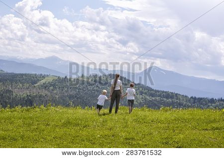 Mother And Two Little Sons Stand Holding Hands On A Green Field Against A Background Of Forest, Moun