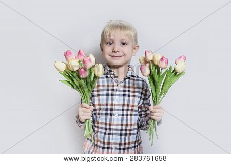 Small Smiling Blond Boy Holding A Bouquet Of Tulips. Portrait On Light Background