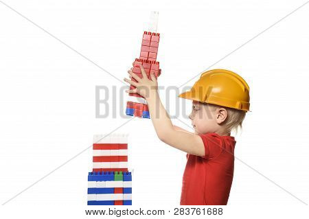 Blond Boy In Construction Helmet And Red T-shirt Builds A Skyscraper From The Details Of The Designe