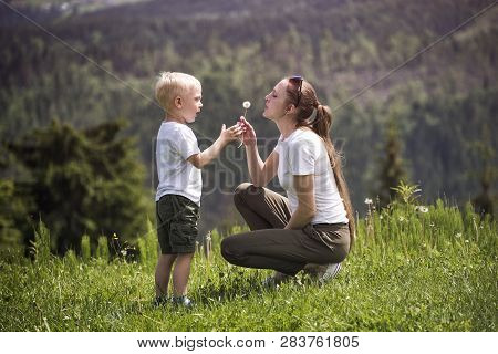 Mother And Little Son Blow Dandelion. Maternity And Friendship.
