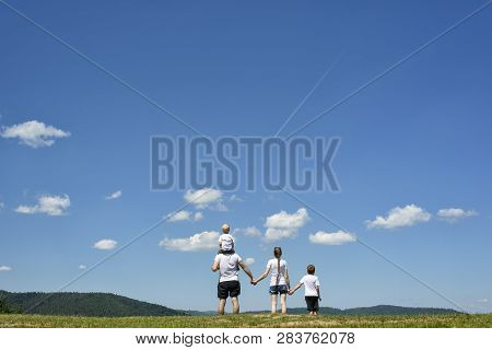 Father, Mother And Two Little Sons Are Standing On A Green Field On A Background Of Wooded Hills, Bl