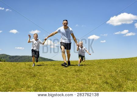 Father With Two Young Children Running Hand In Hand On The Green Field On A Background Of Blue Sky A