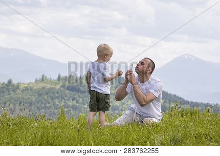 Father And Young Son Are Blowing Dandelions Sitting In The Grass On A Background Of Green Forest, Mo