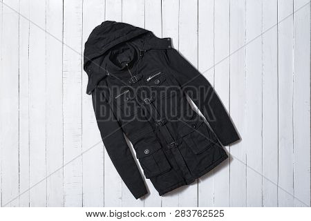 Fashion Clothes. Black Women Coat With Hoodie On White Wooden Floor Planks