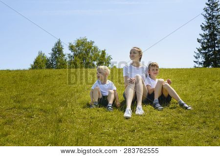 Mother And Two Young Sons Sitting On Grass On A Background Of Trees And Blue Sky.