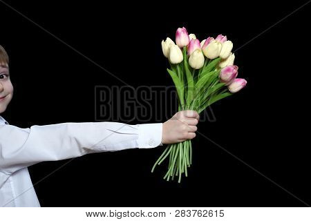 Little Boy In White Shirt Gives A Bouquet Of Tulips. Isolate On Black Background